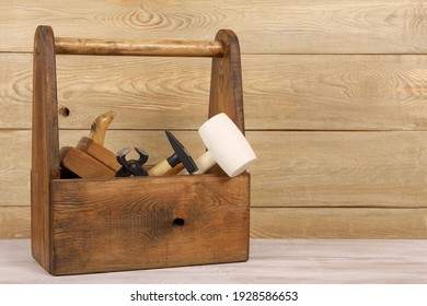 wooden box of carpenter tools on the table, near wall