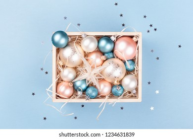 Wooden box with Christmas decorations on blue background decorated with confetti. Top view.
