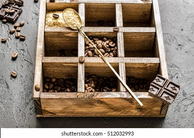Wooden box with coffee beans, dark chocolate and brown sugar in spoon, close-up, on black texture background