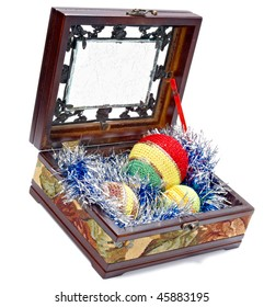 Wooden box with colourful balls made of knitted wool. Studio shot on a white background, not isolated.