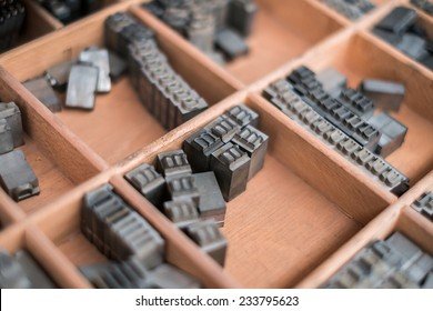 A wooden box containing type script letters - Typography
