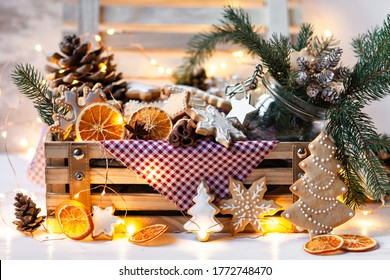 Wooden box with delicious homemade gingerbread cookies with white icing. Perfect beautiful gift in rustic style. Orange, cones, fir tree branches and lights as decor. Close up. Cozy home atmosphere - Shutterstock ID 1772748470