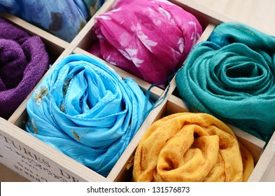 Wooden box with different colorful scarves
