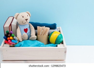 Wooden box with donations: children's toys, stationery and children's clothing. Concept: you can help, they need help. Background, free space for inscription. Red heart on the chest of a teddy bear.