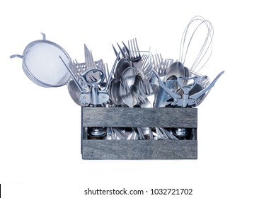 Wooden box filled with stainless steel kitchen cutlery. White cutout background.