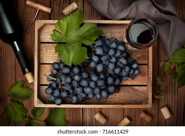 wooden box with grapes and a glass of wine, a bottle of wine on the old wooden background. view from above