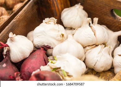 A wooden box of organic white garlic and red onions. Farmers market, healthy eating concept.
