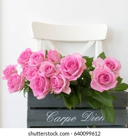 Wooden box with pink roses on wooden chair