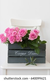 Wooden box, pink roses on white wooden chair and olive tree leaves