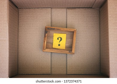 Wooden box with question mark inside cardboard box. Concept image. Close up.