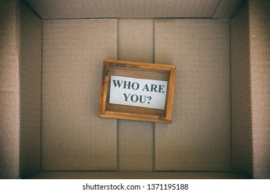Wooden box with question Who are you inside cardboard box. Concept image. Close up.