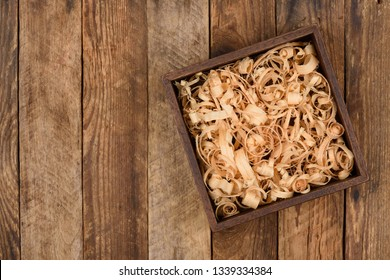 Wooden box with shavings straw filling on table. Top view.