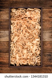 Wooden box with shavings straw filling on table. Wine bottle crate. Top view.