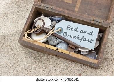 """Holzkiste mit Schalen, Steinen, Schlüssel und Karte mit dem Text """"Bed and Breakfast"""" / Bed and Breakfast / Strandurlaub"""