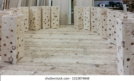 Wooden box standing on the floor of carpenter workshop. Box is filled with wood shavings. Shavings have the smell of the forest. Bright and natural color of the wood. Handmade craft.