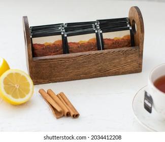 Wooden box of tea bags, tea cup, lemon, cinnamon pods.