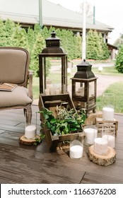 Wooden boxes, lamps and white candles in decoration of a stylish modern wedding.