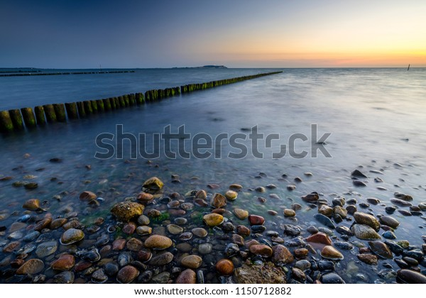 Wooden breakwaters with colorful stones in front during a cloudless sunset in Dranske, Ruegen, Germany