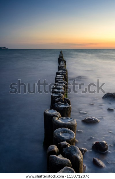 Wooden breakwaters pointing towards the sunset in Dranske, Ruegen, Germany