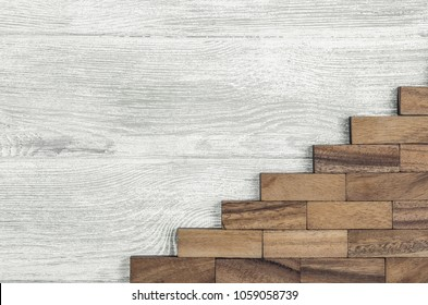 Wooden bricks laid out in the form of  ladder up on a gray wooden background. The concept of day of work, top view.