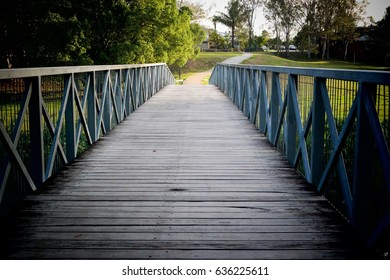 A wooden bridge across a creek in a park with green scenery and forest