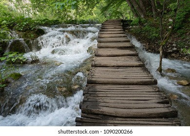 Wooden bridge across the flowing water of the lakes in Plitvice Lakes National Park in Croatia