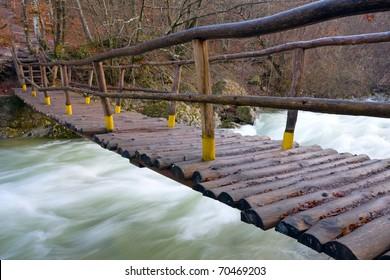 Wooden bridge across mountain river