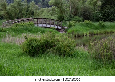 Wooden bridge across a river. Taken in Willband Creek Park, Abbotsford, British Columbia, Canada.
