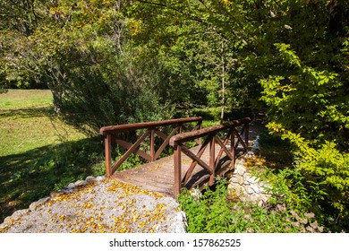 Wooden bridge in the autumn park. Wooden  footbridge on an early fall day