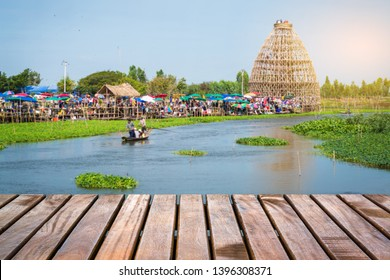 Wooden bridge with blur floating market in the background at Wat Thong Pradit, Song Phi Nong, Suphan Buri, Thailand
