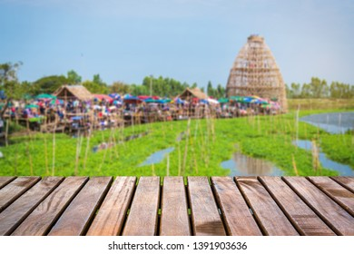 Wooden bridge with blur giant coop fish trap made by bamboo and the floating market in the background at Wat Thong Pradit, Song Phi Nong, Suphan Buri, Thailand