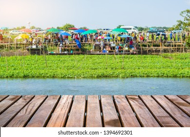 Wooden bridge with blur people enjoying shopping in the floating market in the background at Wat Thong Pradit, Song Phi Nong, Suphan Buri, Thailand
