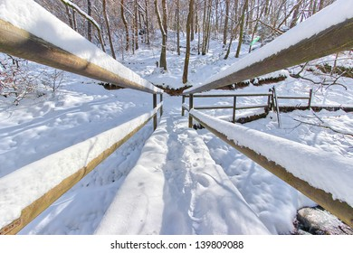 Wooden bridge covered by snow in a forest of eastern Belgium