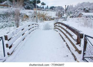 WOODEN BRIDGE COVERED BY SNOW IN PUBLIC PARK.