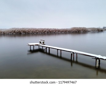 Wooden bridge covered with snow on small river. Beautiful graphic blank. Copy space.