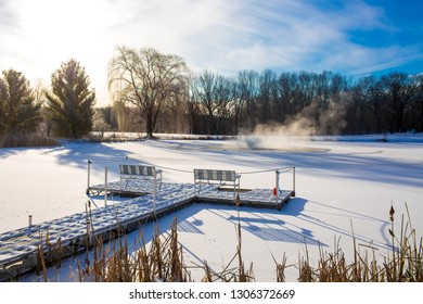 Wooden bridge covered with snow on small lake. Frozen lake