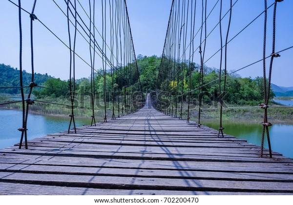 A wooden bridge extends to the mountains, it is a good sight seen far away.