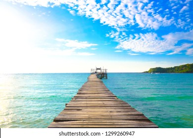 Wooden bridge extends to the sea with mountain against blue sky.