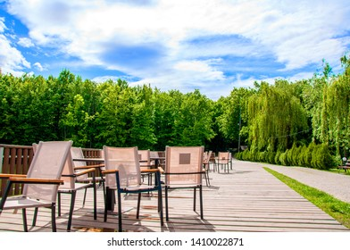 wooden bridge with a fence on which tables and chairs are located. Summer cafe. It's summer outside. The sun is shining. On the background of green forest