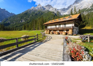 Wooden bridge flowers stable building in the background and green pasture mountain valley, Fischleintal, Val Fiscalina Pustertal, Sudtirol, Italy