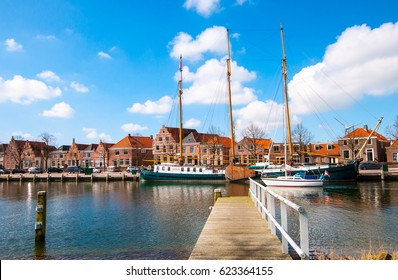 Wooden bridge at harbour with sailing boats in Medemblik city with beautiful blue sky clouds, Netherlands