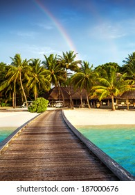 Wooden bridge to island beach resort, beautiful colorful rainbow over fresh green palm trees, luxury hotel on Maldives island, summer vacation concept