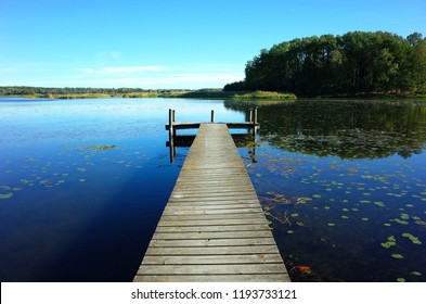 Wooden bridge in lake with calm water and blue sky in Sweden, Scandinavia, Europe. Peaceful outdoor image on Malaren lake in Vastmanland