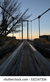 Wooden bridge leading to a beach at sunset.  The bridge is crossing the Two Hearted River in the Upper Peninsula of Michigan.