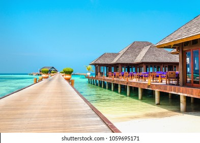 A wooden bridge leading to a luxury resort on the water, Maldives