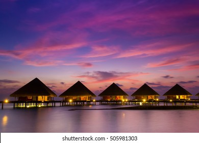 Wooden bridge leading to the Water bungalows with beautiful twilight sky and sea in Maldives. Long Exposure.