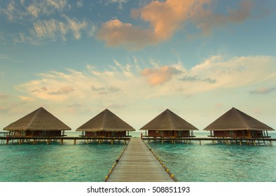 Wooden bridge leading to the water private bungalows with beautiful sky and sea in Maldives.