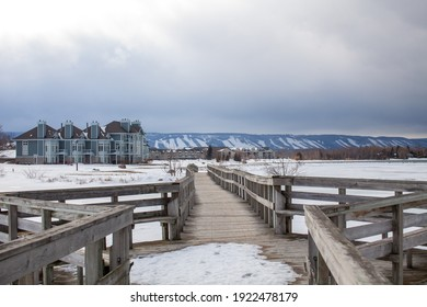 A wooden bridge in Lighthouse Point, Collingwood, crosses a portion of Georgian Bay while overlooking the Blue Mountain Ski hills from a distance, with the frozen water beside it