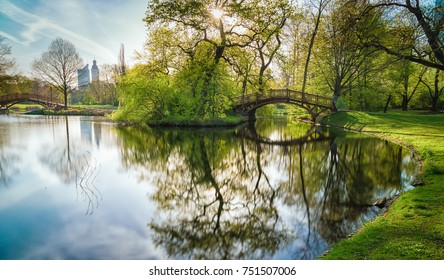 Wooden bridge with a mirroring lake in Johanna Park Leipzig, in the background the City-Hochhaus and the tower of the city hall