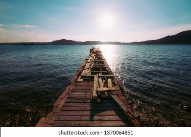 Wooden bridge on the beach to the sea in afternoon summer sky.